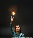 Asian businesswoman reaching for light bulb symbollically grabbing new ideas and creativity.